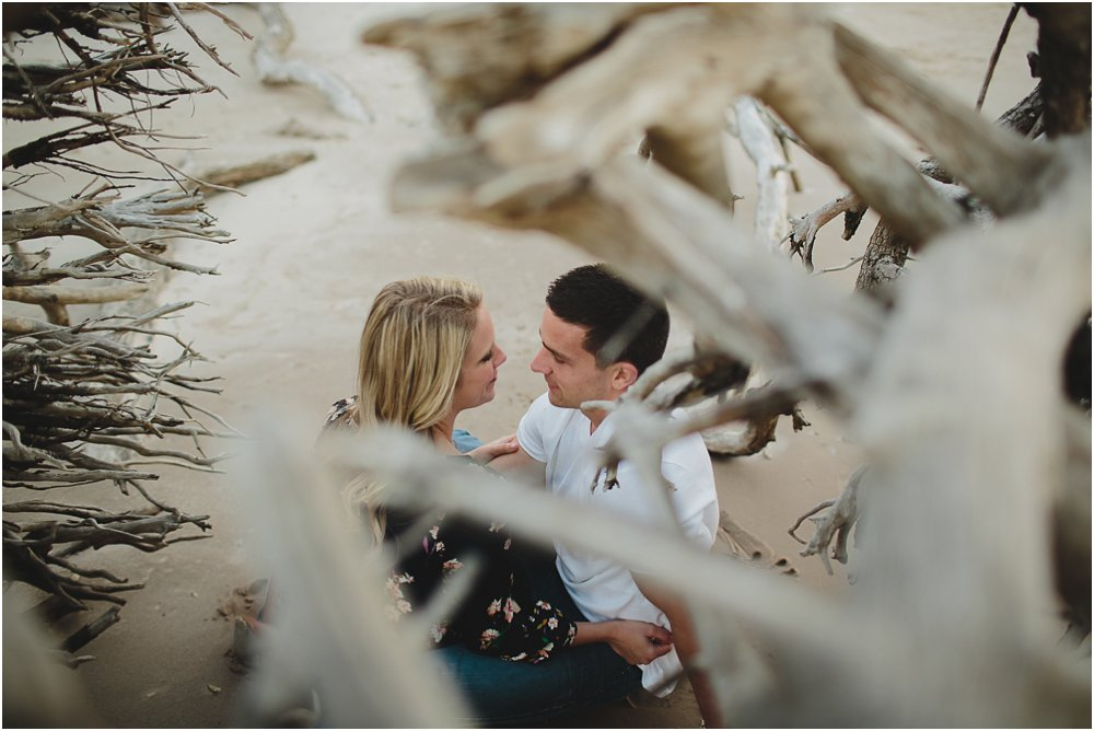 couple looking at each other with driftwood around them