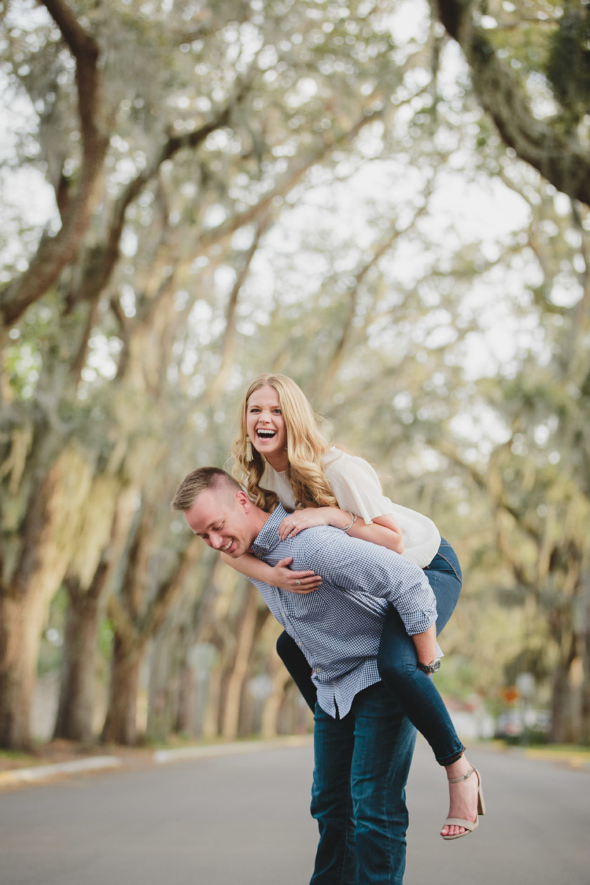 woman hopping on man's back and laughing