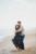 man hugging woman from behind standing on beach in ponte vedra