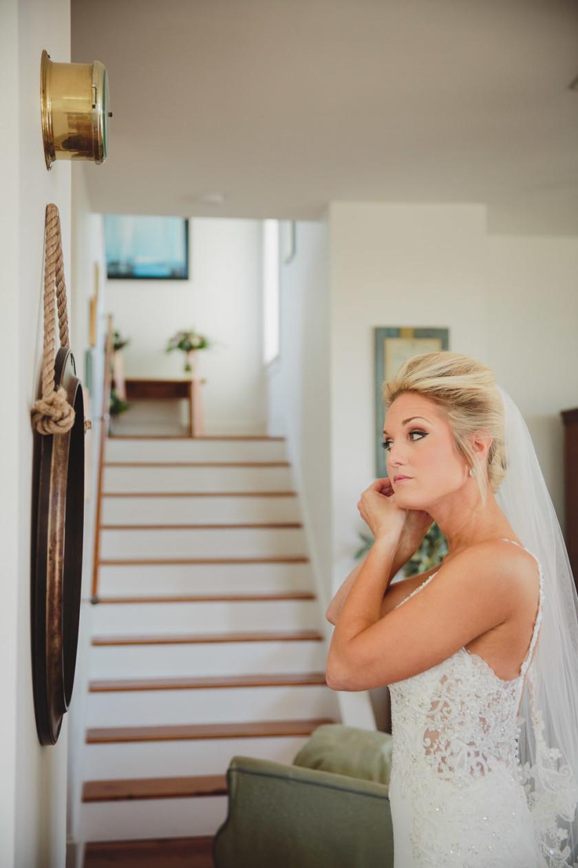 bride looking in mirror putting on wedding earrings