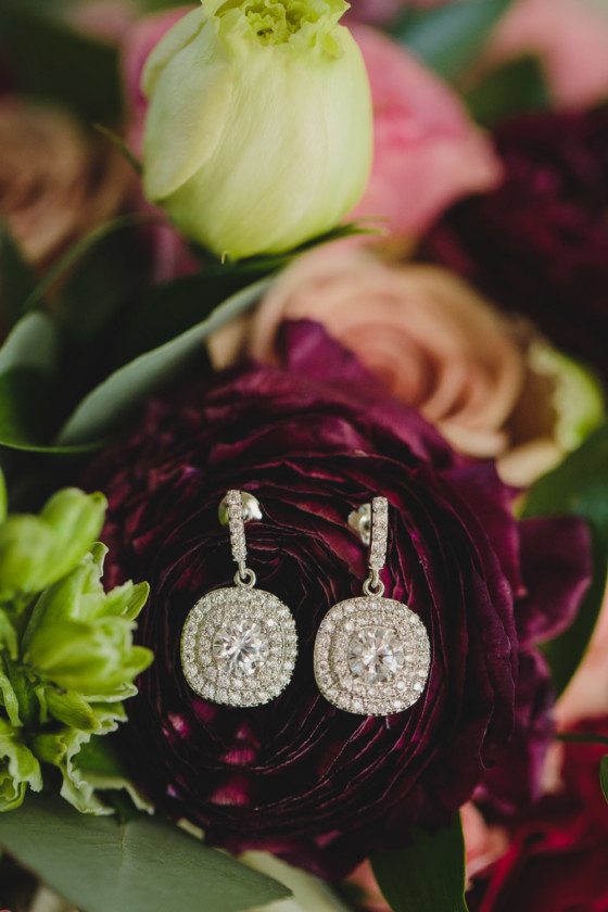 bridal earrings laying on deep red floral bouquet