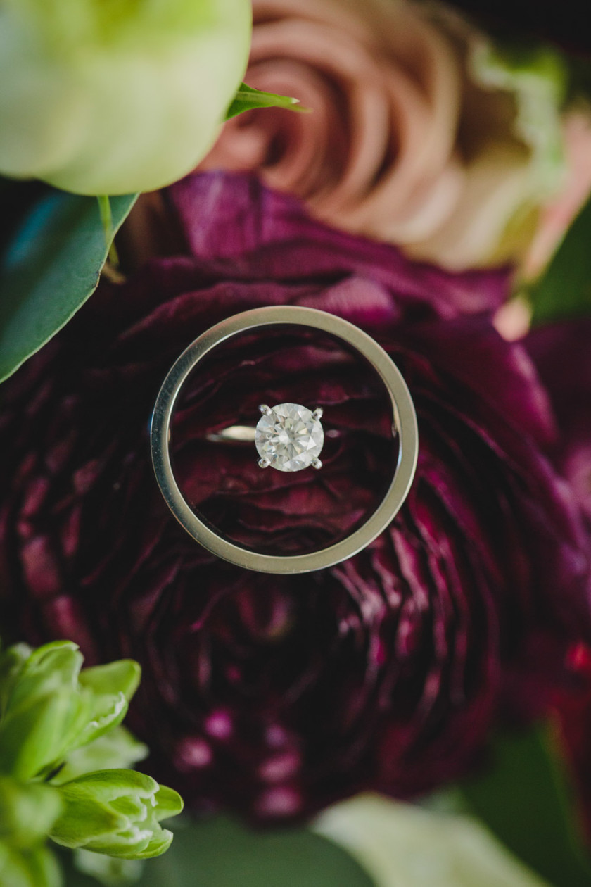engagement ring and wedding band laying on burgundy floral