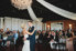 bride and groom dancing under grand ballroom chandelier