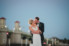 bride and groom kissing in front of bridge of lions