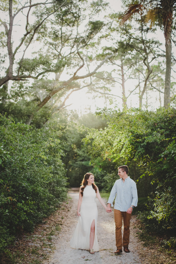couple holding hands while walking in woods