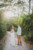 couple looking back and walking on dirt path through woods
