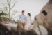 couple walking on beach with fallen trees