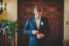 groom buttoning up his suit standing in front of two wooden doors
