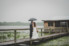 groom and bride kissing under umbrella while walking on dock over lake