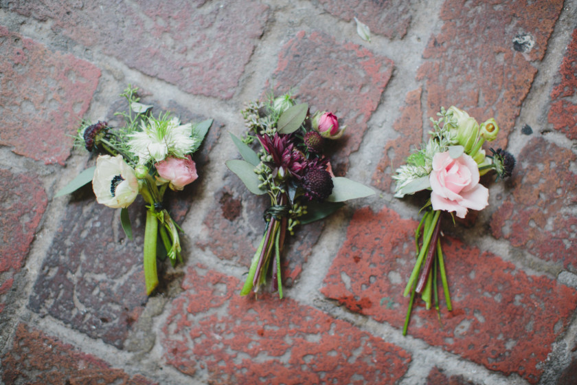 boutonnieres laying on brick floor