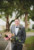 groom standing in front of ribault club holding bridal bouquet