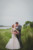 bride and groom about to kiss with river in background and tall grass
