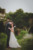 groom and bride about to kiss in grassy field with trees in background