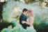 bride with pink hair hugging groom with green smoke surrounding them