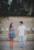 couple holding hands looking at each other in front of stone wall with fountain