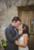 groom pulling bride in for kiss in front of wooden door