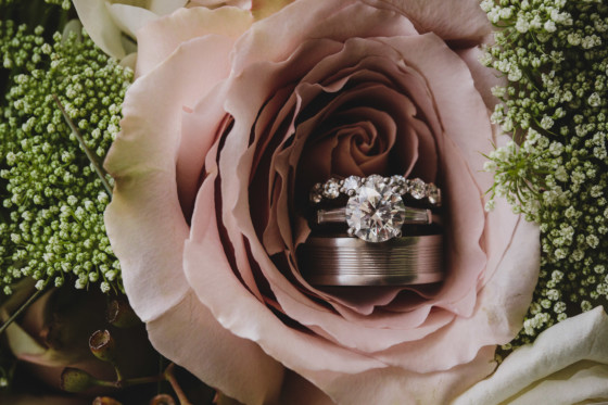 engagement ring and wedding bands arranged in dusty rose flower