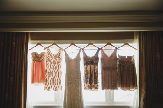 bridal gown and bridesmaid dresses hung up all together in a line