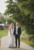 bride and groom holding hands, standing in pathway under trees