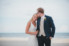 groom kissing bride's forehead while standing at the beach