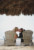 bride and groom sitting in wooden chairs kissing
