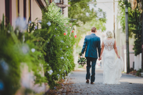 bride and groom walking down cobble street