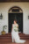bride looking to the side holding bouquet standing in front of door