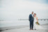 bride and groom standing on beach