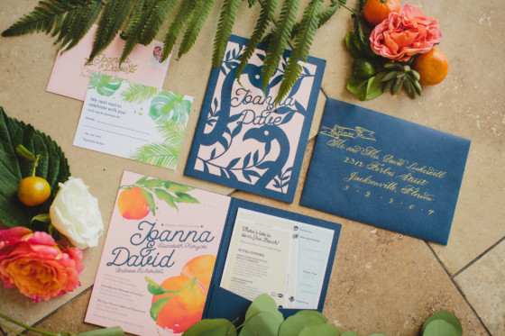 wedding invitation with citrus and flamingos on them