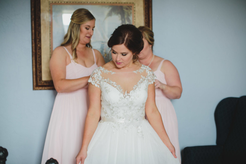 bride getting wedding gown zipped up by bridesmaids