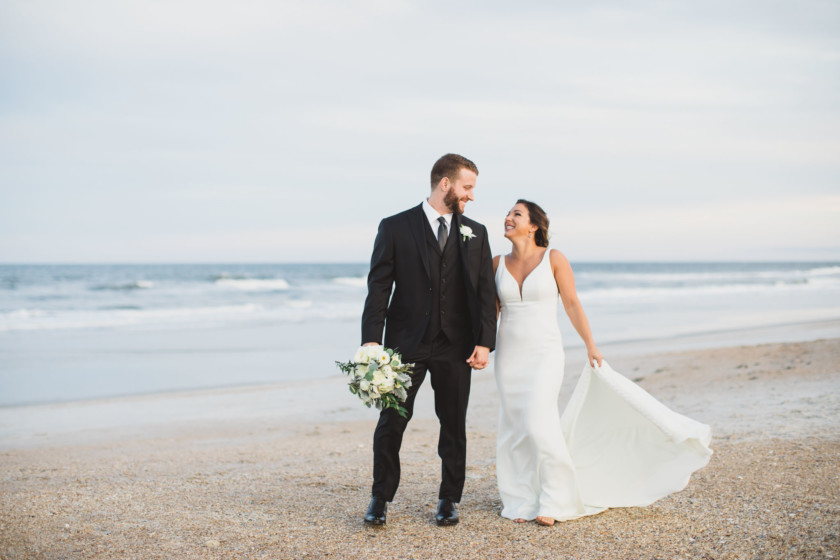 bride and groom looking toward each other while standing on ponte vedra beach