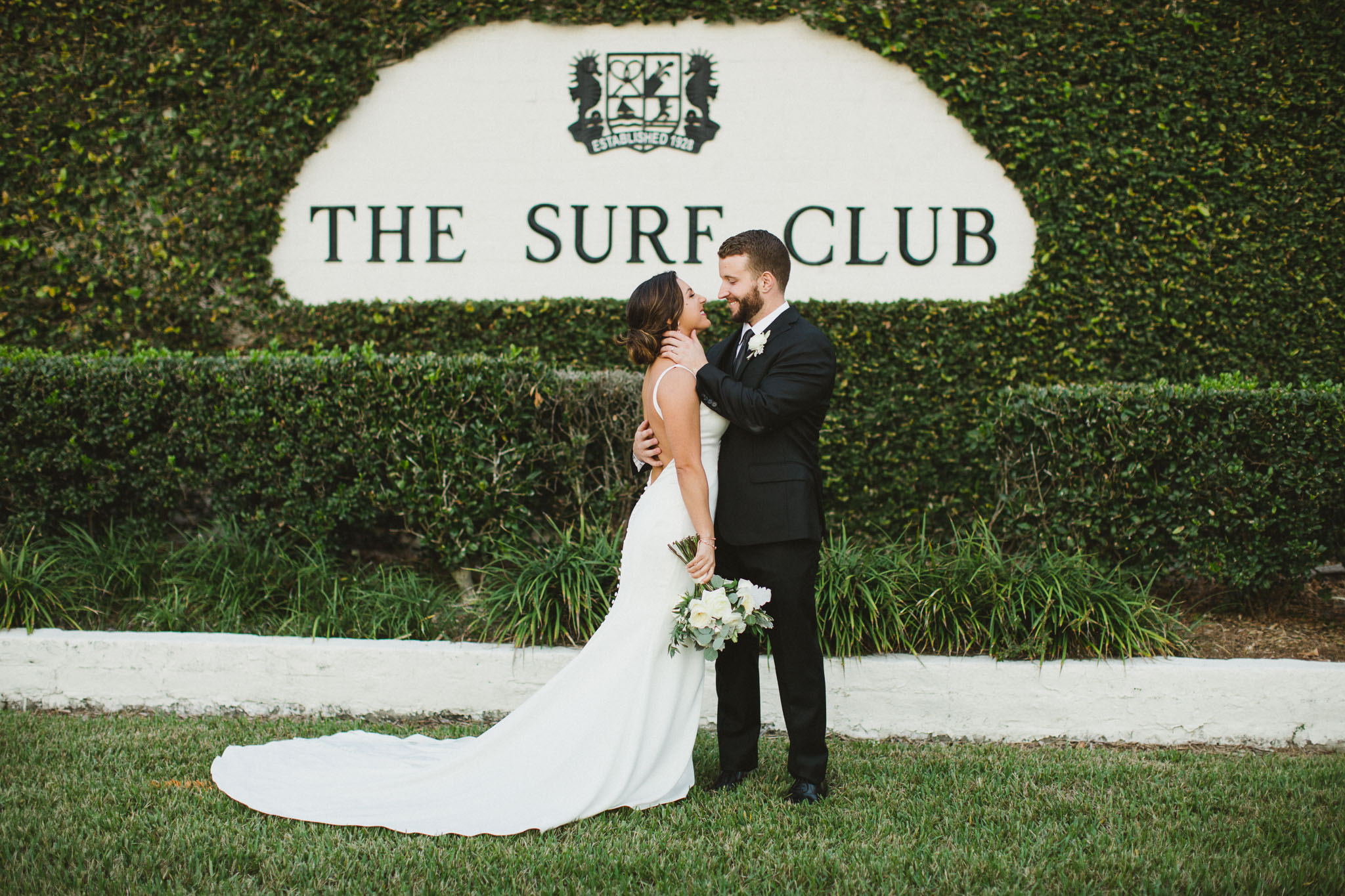 bride and groom looking at each other in front of surf club sign