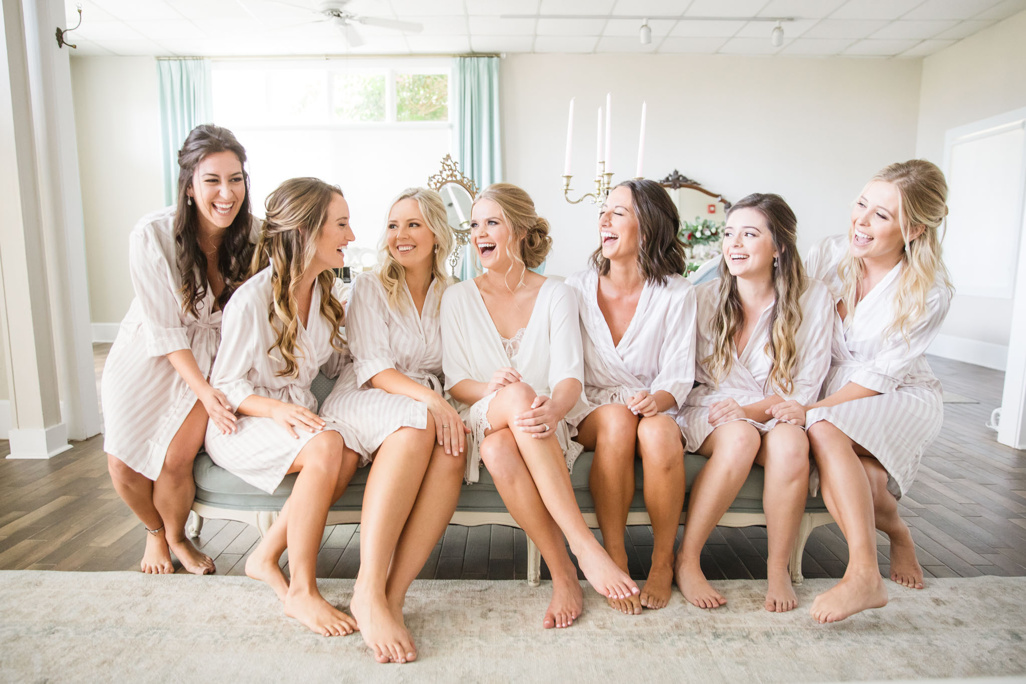 bride with her bridesmaids sitting on sofa laughing in white room bridal suite
