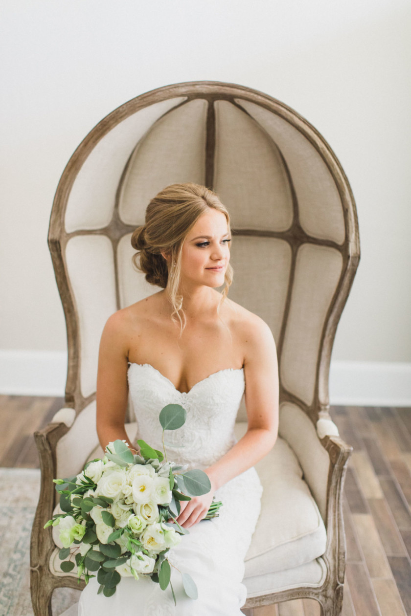 bride sitting in chair with cone back holding her all white florals bridal bouquet