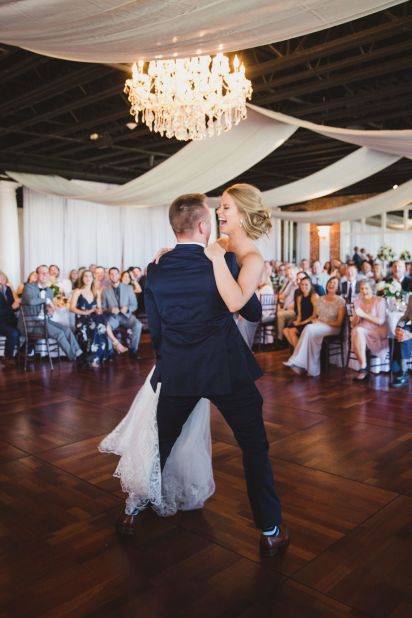 groom lifting bride off her feet on dance floor during first dance in grand ballroom