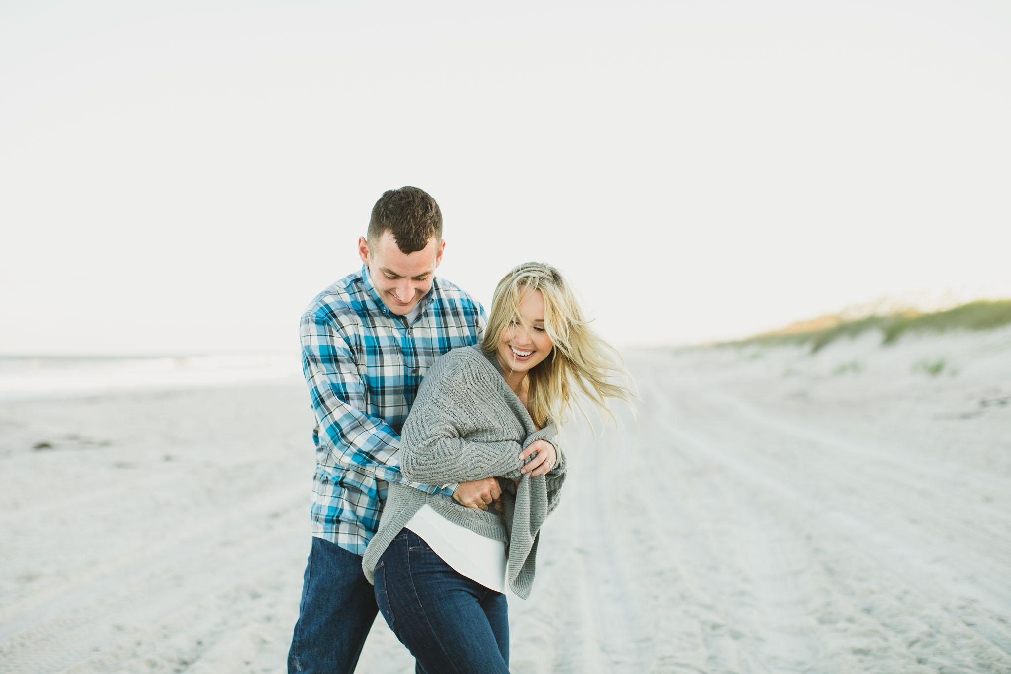 man hugging woman from behind at beach