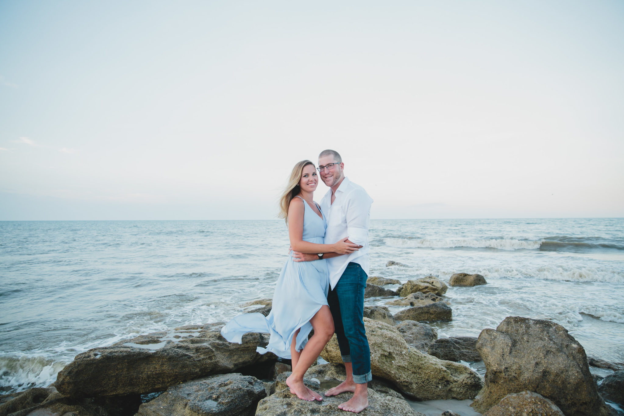 couple on rocks at beach during engagement session