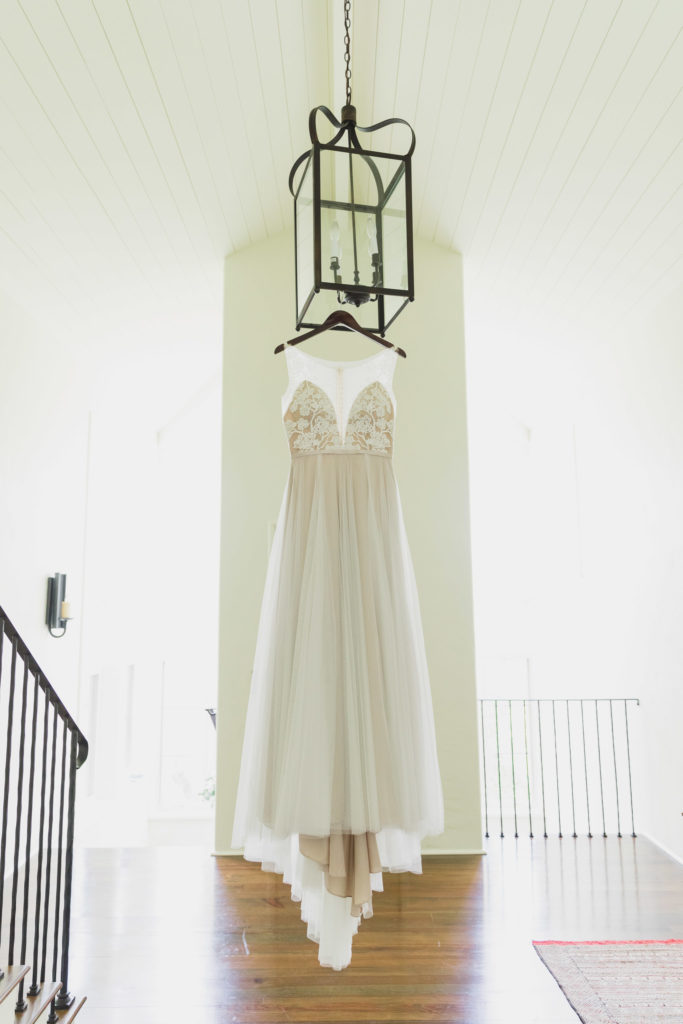 wedding gown hanging from light fixture in tall room