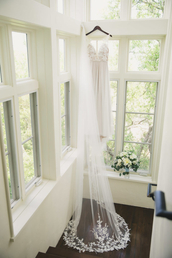 bridal gown and wedding veil hanging at windows