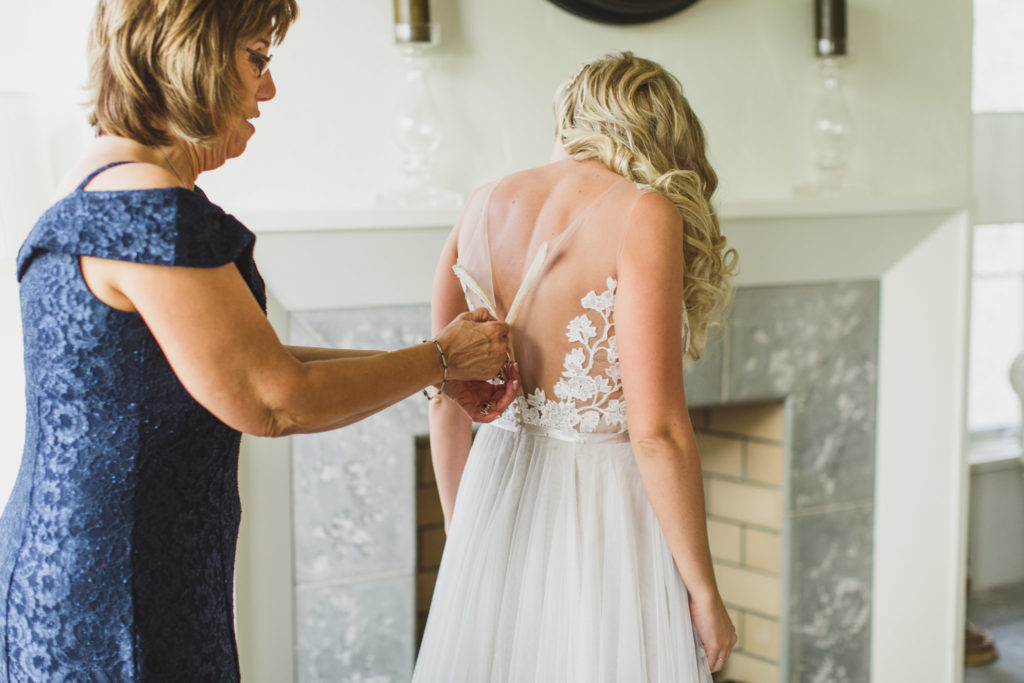 bride getting gown zipped up by mom