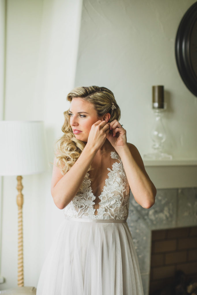 bride putting on wedding earrings looking out window