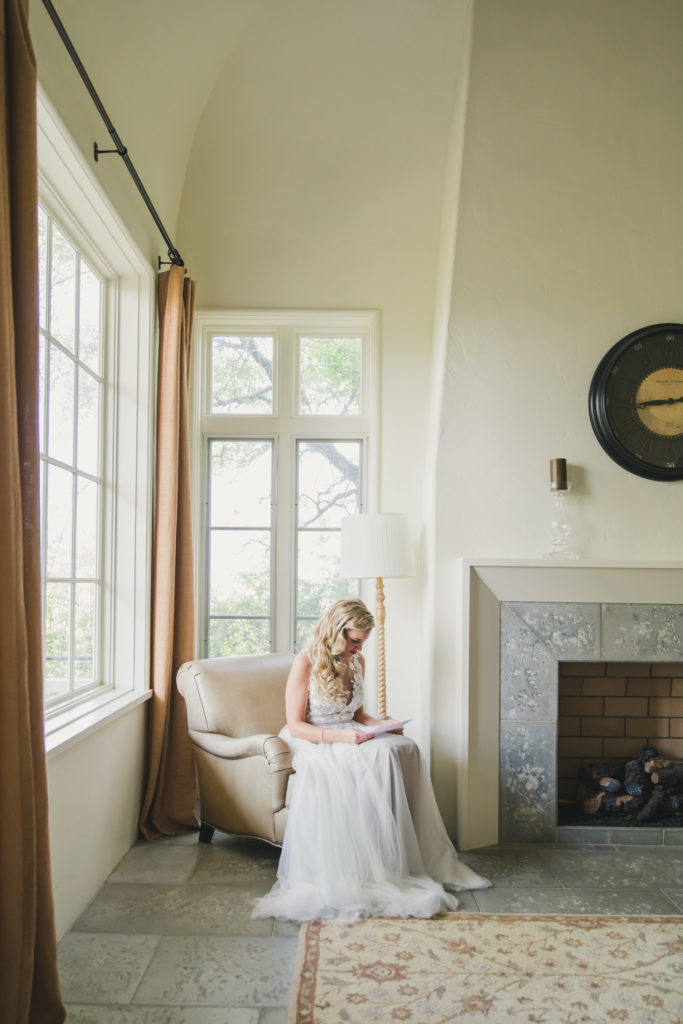 bride sitting on chair reading note from groom