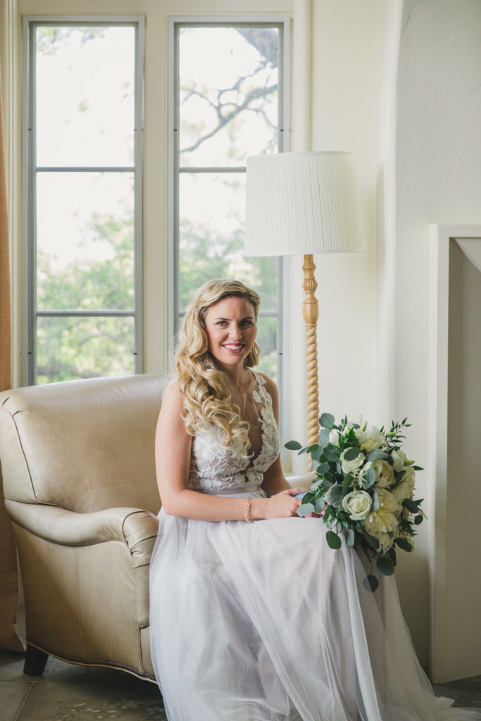 bride sitting on chair holding bouquet