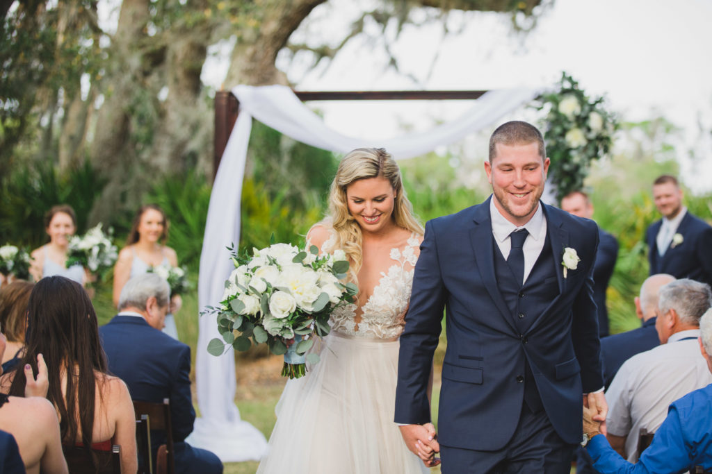 bride and groom holding hands walking down aisle