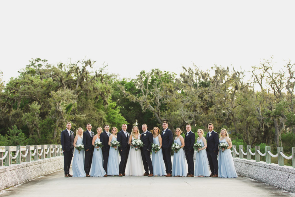 wedding party lined up standing on bridge