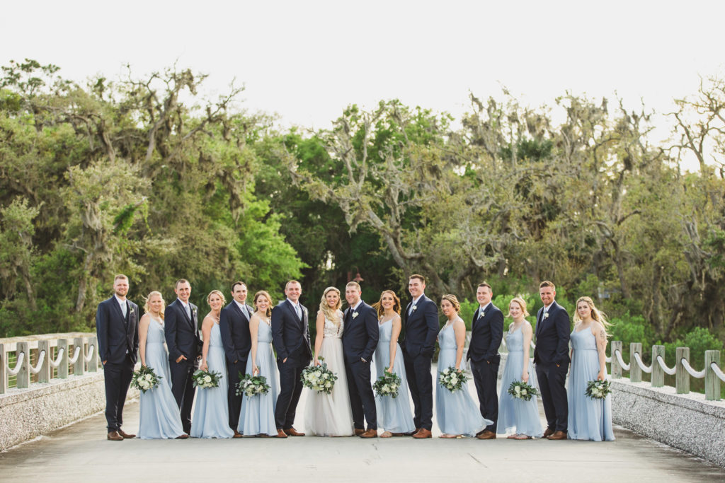 wedding party standing on bride with trees in background
