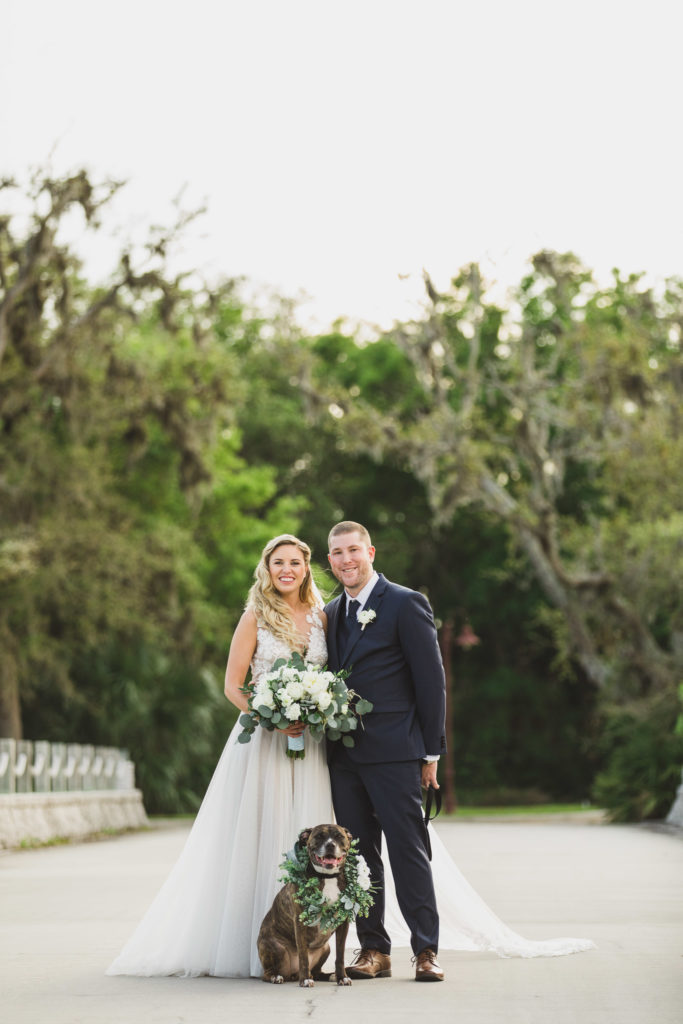 bride and groom and flower girl dog standing in middle of bridge road in amelia island