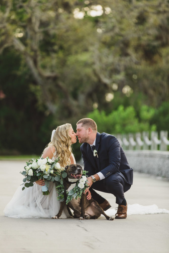 bride and groom kissing and squatting down with flower girl dog