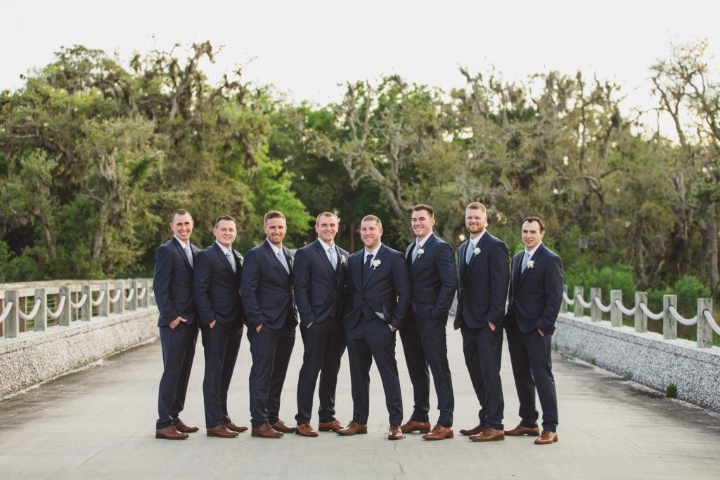 groom and groomsmen on bridge road