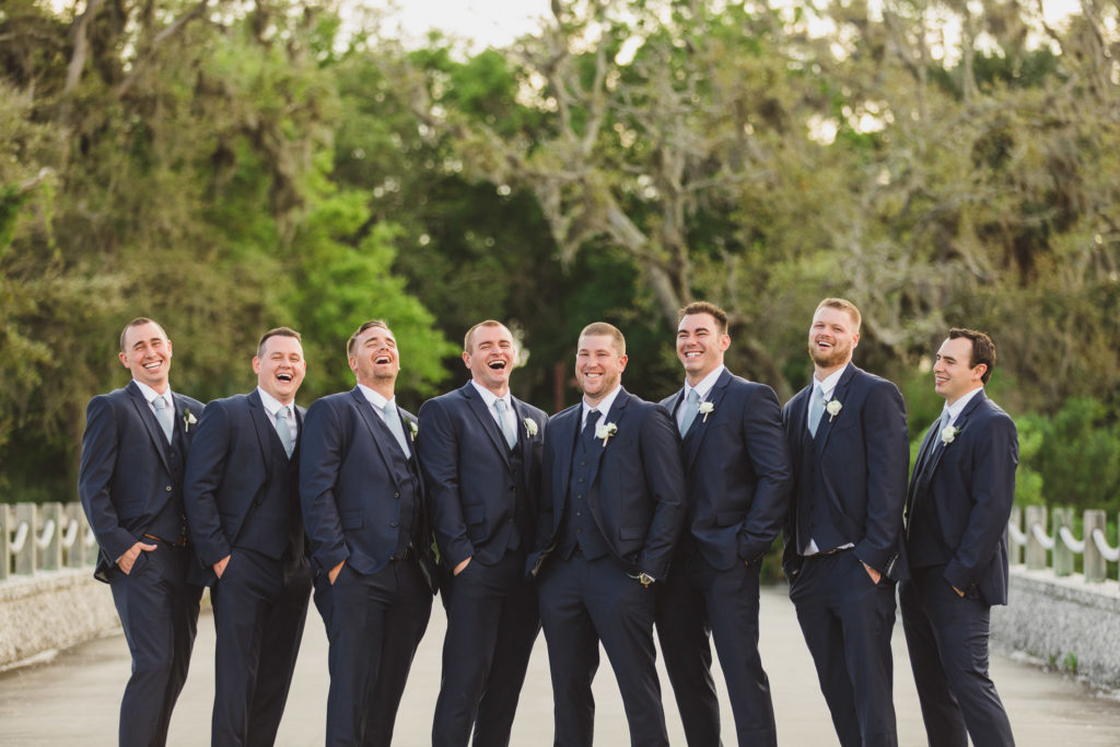 groom and groomsmen standing together in road